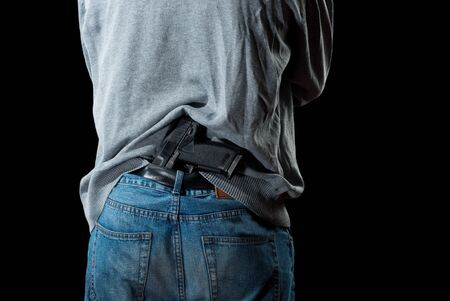 gun man: Man`s back with gun tucked in pants. Isolated on white background.