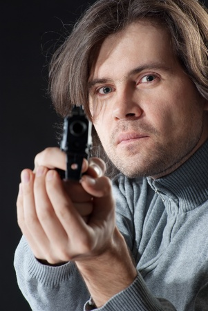 A man with long hair tacking aim. photo