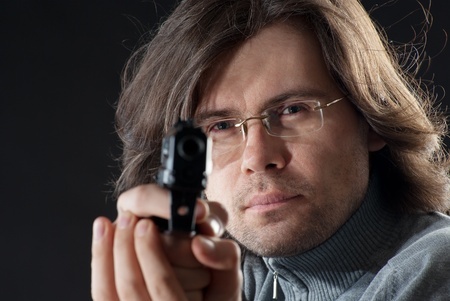 A man in eyeglasses tacking aim.  photo