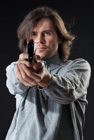 Man with long hair pointing a gun  photo