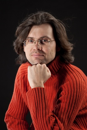 hand on chin: Man with log hair in red sweater and glasses.