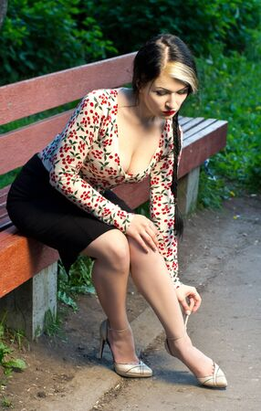 Glamour brunette caucasian woman sitting on a bench. photo
