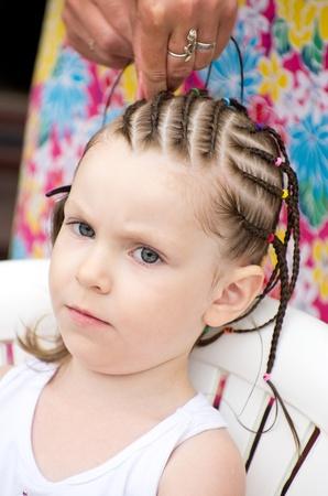 hair stylist: Hairdresser hands weaving a dreadlocks for little girl.