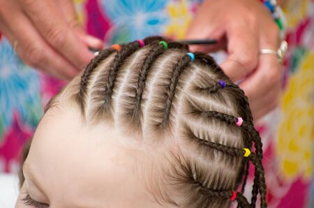 plait: Hairdresser hands weaving a dreadlocks for little girl.