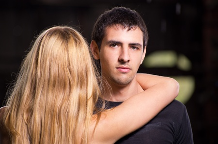 Fashion shot of a young handsome man embracing long hair blonde woman against urban background. Stock Photo - 10354311