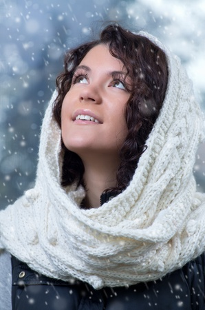 Pretty young caucasian brunette woman wearing white scarf with hood in a outdoor winter portrait  photo