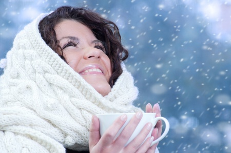 warm drink: Pretty young caucasian brunette woman wearing white scarf with hood in a outdoor winter portrait