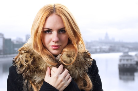 Young caucasian beautiful  redhead  woman against urban background. photo