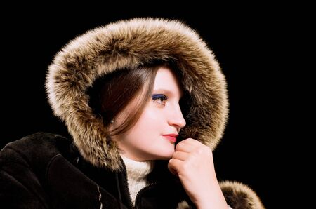 sheepskin: Beautiful woman in winter fur coat. Isolated on black background.