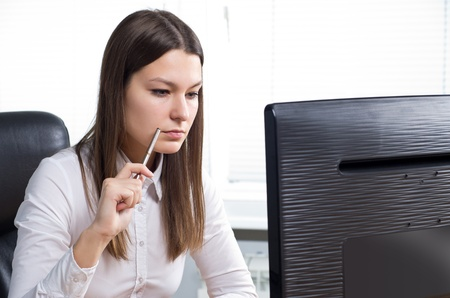Attractive young caucasian brunette businesswoman sitting in her office Stock Photo - 12128293