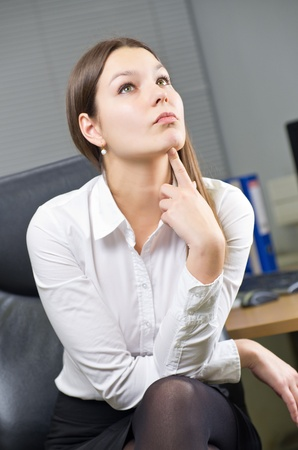 Attractive young caucasian brunette businesswoman sitting in her office photo