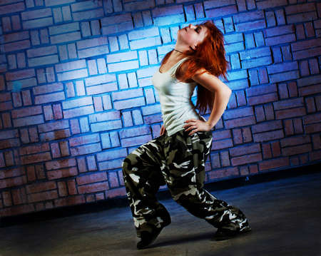 Hip hop girl dancing in modern style over urban blue brick wall Stock Photo - 12378938