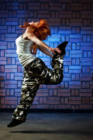 Hip hop girl dancing in modern style over urban blue brick wall Stock Photo - 12378937