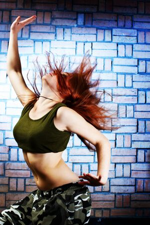 Hip hop girl dancing in modern style over urban blue brick wall photo