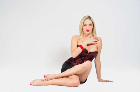 Attractive sexy young caucasian blonde woman sitting on the floor photo