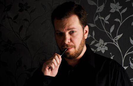Portrait of young caucasian man wearing black shirt smocking e-cigarette