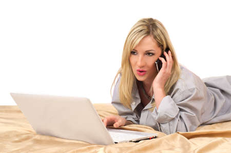 Studio portrait of young beautiful caucasian blonde woman with laptop calling on bed against white background  Stock Photo - 12713260
