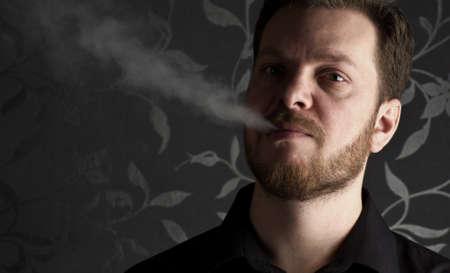 smocking: Portrait of young caucasian man wearing black shirt smocking.