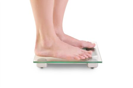finders: Closeup shoot of young caucasian woman legs on scales  Isolated over white background