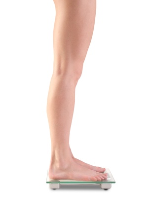 finders: Shoot of young caucasian woman legs on scales. Isolated over white background Stock Photo