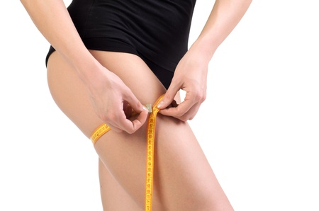 Closeup of a sexy young woman measuring her haunch. Isolated over white background