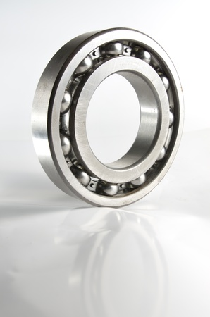 Ball bearing with reflection over white background.