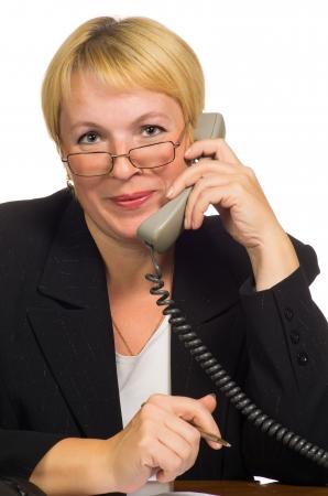 calling: Empresaria madura llamando por tel�fono a su lugar de trabajo aislado sobre fondo blanco