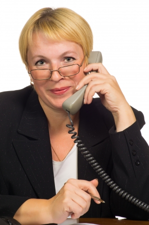 calling on phone: Mature businesswoman calling on the phone at her workplace  Isolated against white background