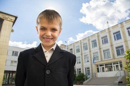 Schooler que sonríe en el patio de la escuela
