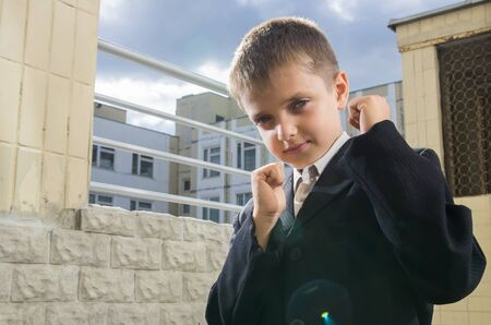 Little schooler Boxing is in front, raising his fists at school yard  photo