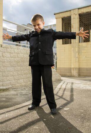 schooler: Piccoli schooler braccia larghe in piedi a cortile della scuola Archivio Fotografico