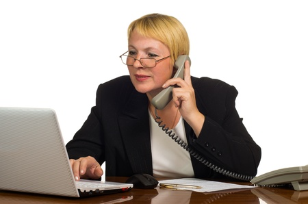 Mature businesswoman calling on the phone and check something on a laptop at her workplace. Isolated against white background.
