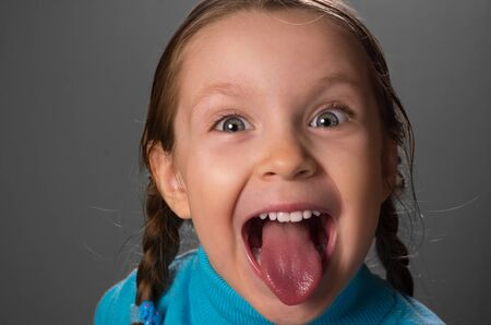 Little girl showing the tongue against grey background, photo