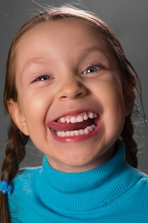 Portrait of little girl showing the tongue against grey background, photo