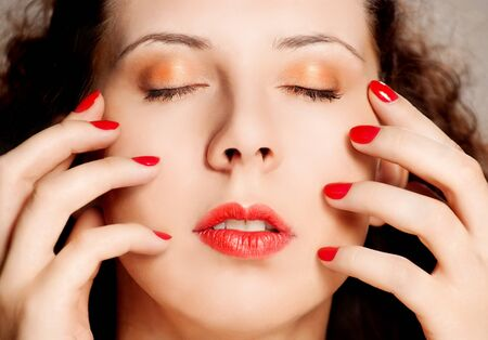 Close-up portrait of caucasian young woman with golden glamour make-up and red bright manicure photo