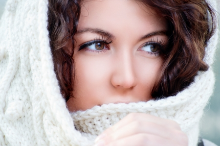 winter woman: Pretty young caucasian brunette woman wearing white scarf with hood in a outdoor winter portrait