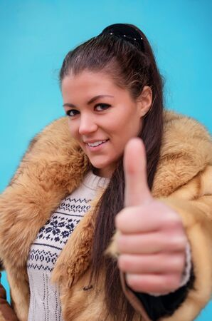 Beautiful woman in a fur coat against blue background showing thumb up photo