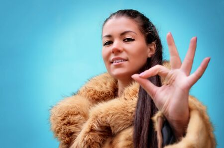 Beautiful woman in a fur coat against blue background showing sign ok photo