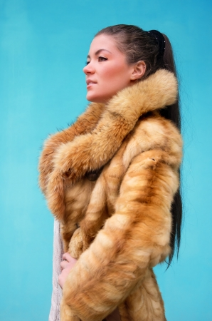 Beautiful woman in a fur coat against blue background photo