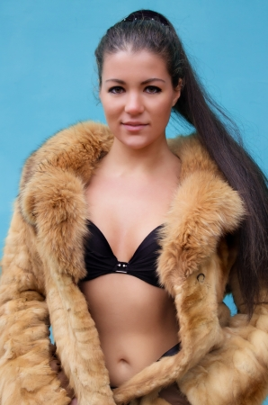 Beautiful nude woman in a fur coat against blue background photo