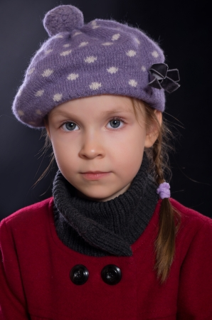 Little girl dressed in red coat and  lilac hat photo