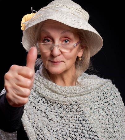 Mature woman in white hat and glasses showing thumb up. Isolated against black background. photo
