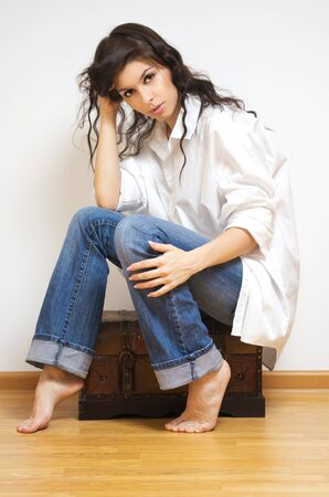 coffer: Beautiful brunette caucasian woman in white man`s shirt sitting on the coffer.
