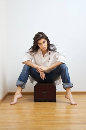 coffer: Beautiful brunette caucasian woman in white man s shirt sitting on the coffer