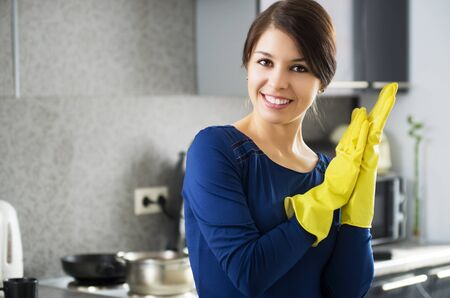 Portrait of young attractive caucasian brunette housewife at kitchen wearing the yellow rubber gloves. photo