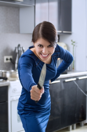 Portrait of young attractive caucasian brunette housewife with knife at kitchen. Stock Photo - 18635468
