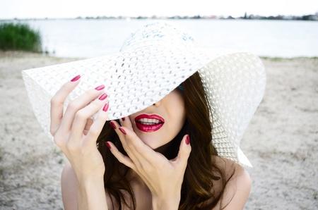 Portrait of beautiful caucasian girl in white hat