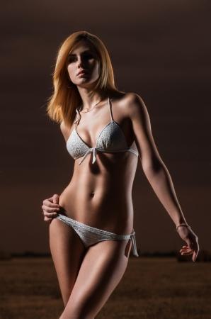 Beautiful young caucasian girl in white bikini near the haystack at the field. Stock Photo