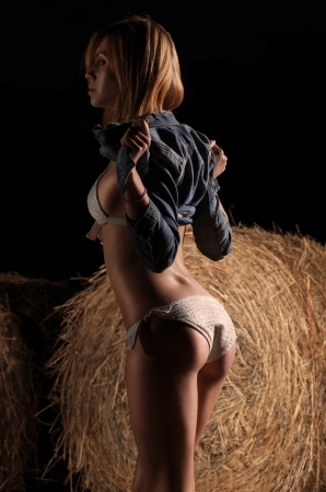 Beautiful young caucasian girl in white bikini and jeans jacket near the haystack at the field.