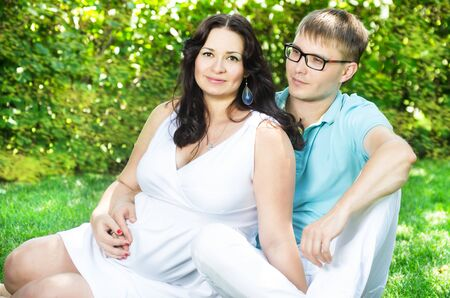 Attractive young caucasian pregnant couple on the lawn at  park photo